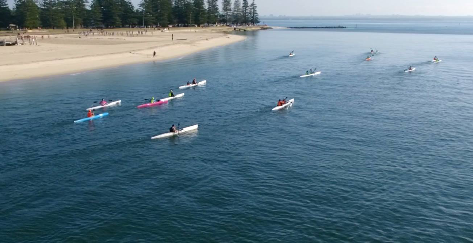 Photo of paddlers on Botany Bay heading towards Doll's Point, past a sandy beach.