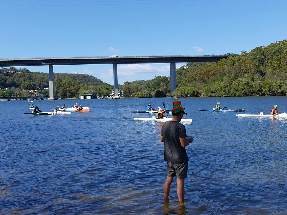 Volunteer timekeeping in foreground. Background: paddlers lining up for a SSCC 5 km TT on the Woronora River