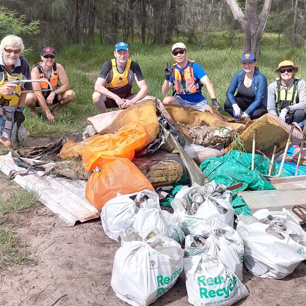 SSCC Volunteers crouch behind pile of collected rubbish