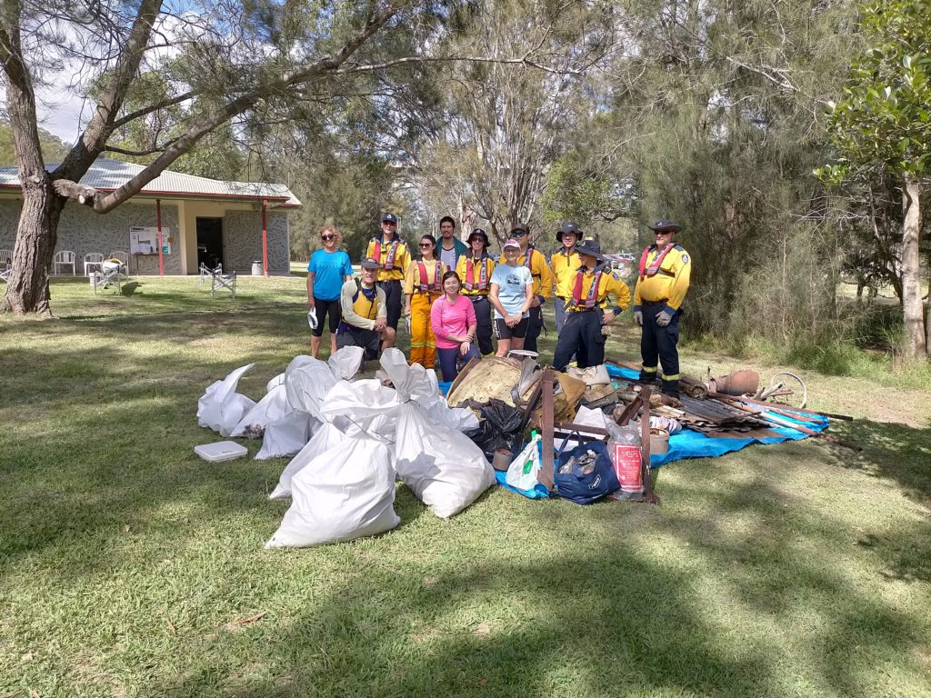 SES + SSCC volunteers standing behind the large pile of collected rubbish