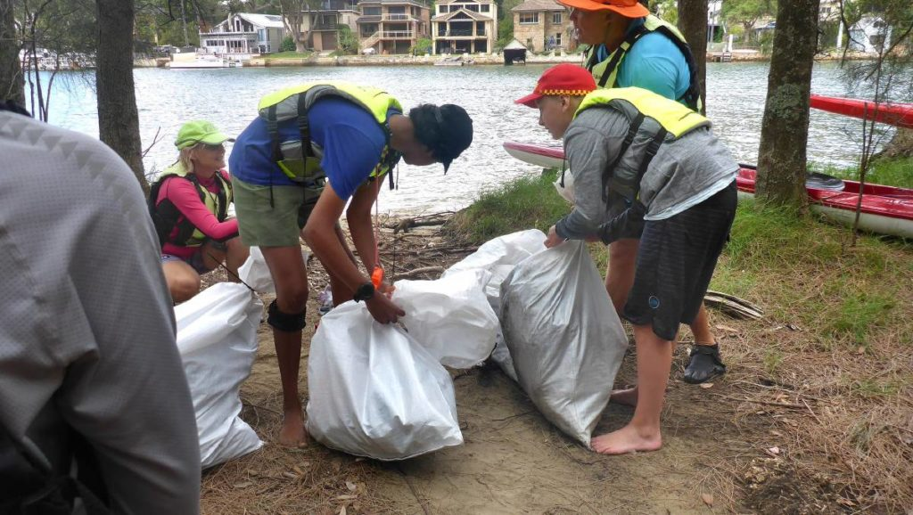 2021-Jan volunteers tying off bags of collected rubbish on the bank of the Woronora River
